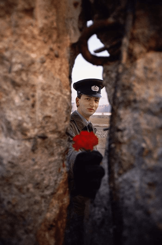 18.) 1989 - East German soldier passing a flower through the Berlin Wall before it was torn down.