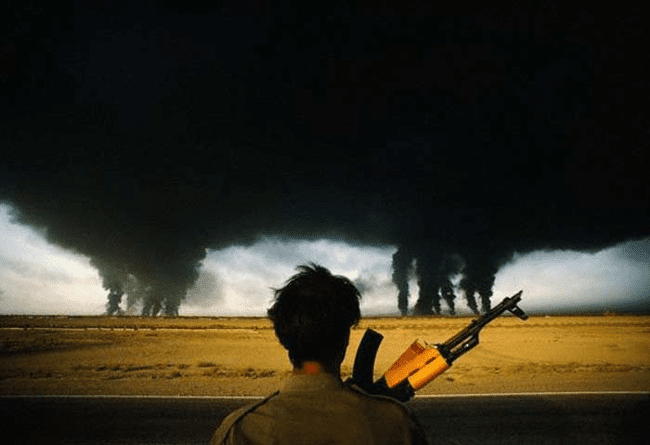 8.) 1990 - Iranian soldiers looks at the burning Iraqi oil fields.