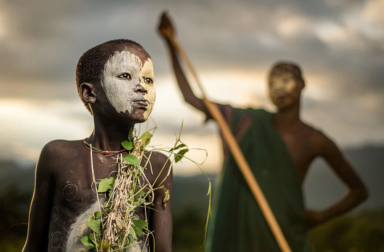 A boy of the nomadic Suri tribe of Ethiopia in traditional face/body paint and attire.