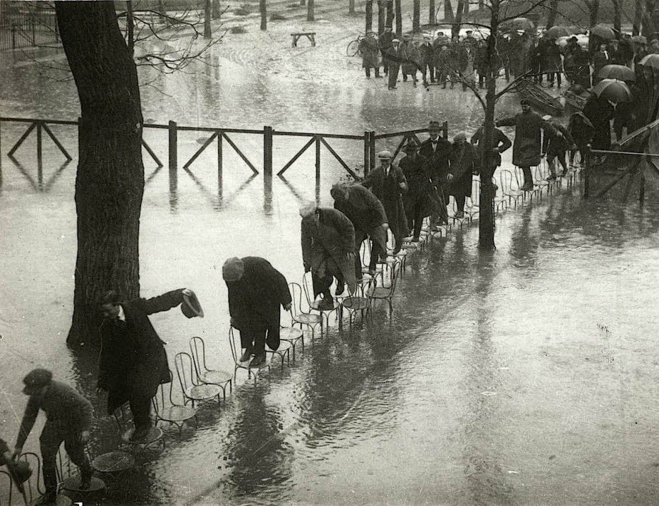Parisians%20navigate%20flood%20waters%20by%20walking%20across%20rows%20of%20chairs.%20%5B1924%5D