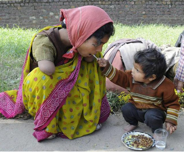 2 -year-old offering food to her handicapped mom.
