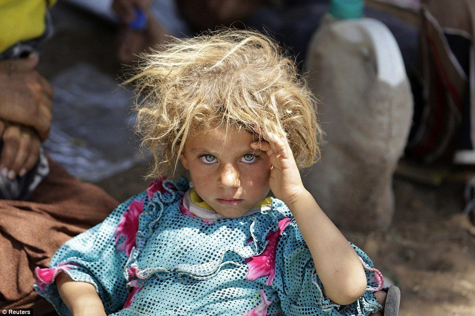A Yazidi girl rests at the Iraqi-Syrian border.